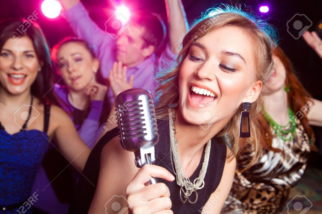 19773289-Young-girl-singing-into-microphone-at-party-Stock-Photo-party-karaoke-entertainment