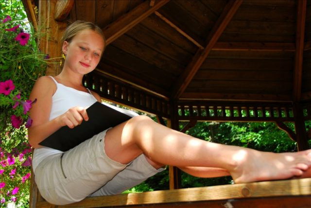 Young girl sitting in a gazeebo reading a book