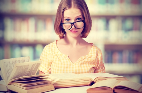 funny crazy girl student with glasses reading books in the library